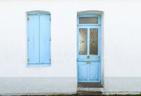 House facade with pastel blue blinds and door