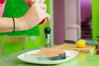 women's hands sprinkle from a handmade mills spices raw steak from salmon