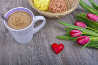 A cup of coffee and red tulips on a wooden table