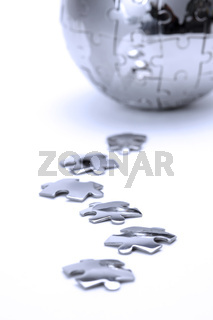 Metal puzzle globe isolated on white background, close-up in blue light