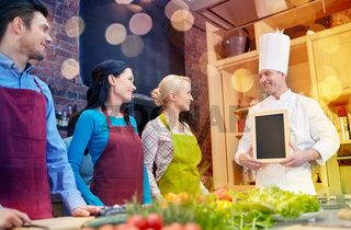 happy friends and chef cook with menu in kitchen