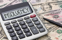 Calculator with dollar bills - Insolvency