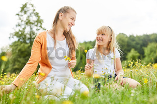 Mutter und Tochter pflücken Blumen zusammen