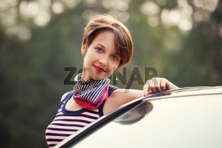 Happy young fashion woman next to her car