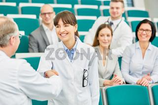 Dozent gratuliert einer Medizin Studentin