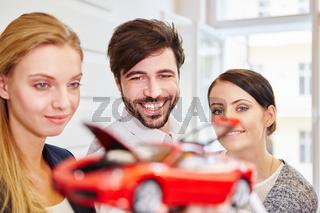 Geschäftsleute betrachten Modellauto
