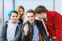 young man showing bitcoin coin to his intrigued group of friends