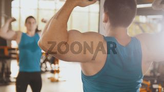 Bodybuilder training in the gym - young muscular man perform training for biceps near mirror