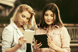 Two young fashion women with using tablet computers outdoor