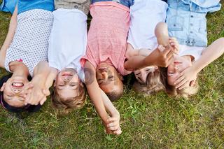 Kinder liegen als Freunde auf dem Gras