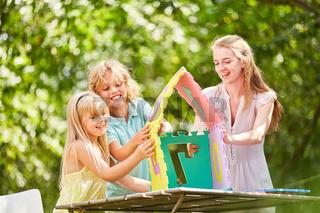 Mutter und Kinder bauen Haus in Teamwork