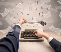 Hand typewriting with flying documents around