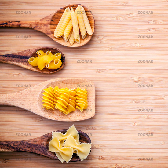 Italian foods concept and menu design. Various kind of Pasta Elbow Macaroni ,Farfalle ,Fusilli  and Penne in wooden spoons setup on bamboo cutting board flat lay and copy space.