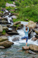 Woman in yoga asana Vrikshasana tree pose at waterfall outdoors