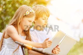 Zwei Kinder spielen mit Tablet Computer im Internet