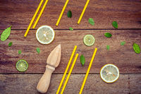 Fresh lemon and wooden juicer for summer juice and cocktail. Fresh lemon sliced ,lime sliced ,yellow straw and peppermint leaves set up on shabby wooden background flat lay.