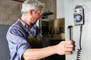 Arbeiter an der CNC Werkzeugmaschine