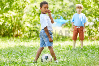 Zwei Jungen spielen Fußball im Park