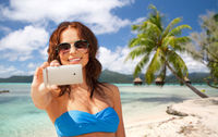 woman taking selfie by smartphone on beach