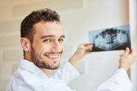 Zahnarzt mit Röntgenbild freut sich