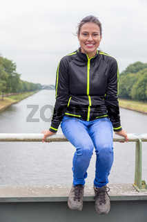 Woman sitting on bridge railing above canal
