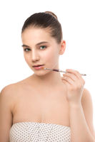 Young brunette woman with clean face. Girl perfect skin applying cosmetic brush. Isolated on a white.