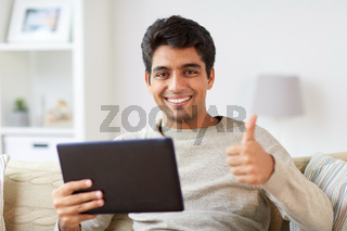 man with tablet pc showing thumbs up at home