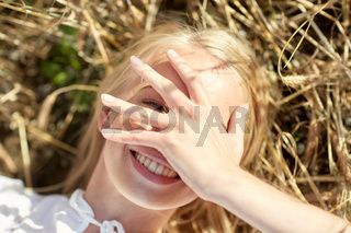 happy young woman lying on cereal field