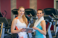 Two young women looking at tablet in gym