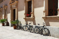 Parked bicycles near a beautiful building in Alcudia, Spain