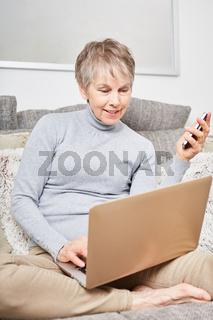 Seniorin mit Laptop Computer online