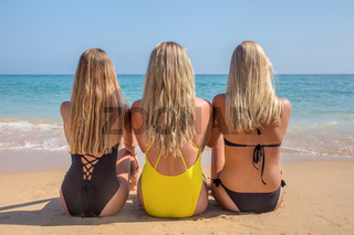 Three blonde dutch girls sit on beach