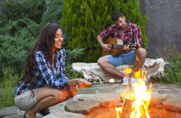 Young couple with guitar near fire outdoors