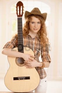 Pretty guitarplayer girl embracing guitar