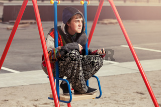 Young fashion hippie man sitting on the swing