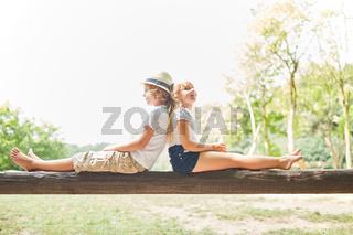 Junge und Mädchen sitzen Rücken an Rücken