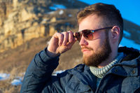 Close-up Portrait of Severe and serious Hipster traveler with a beard in sunglasses in the nature.