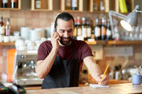 happy man or waiter at bar calling on smartphone