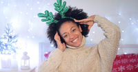 Playful young woman wearing green reindeer antlers