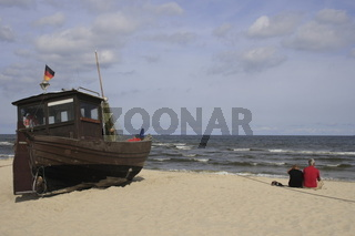 Paar sitzt neben Fischerboot am Ostseestrand