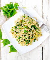 Couscous with spinach and green peas in plate on board top