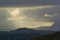 Regenwolken mit Sonnenstrahl über den schottischen Highlands