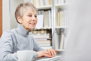 Seniorin arbeitet am Computer online