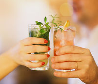 Two cocktail glasses in man and woman hand