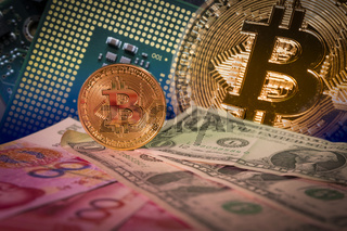 Financial growth concept with golden bitcoin above dollar and yuan bills