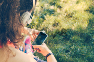 Cropped image of a girl in headphones listen to music and use a smart phone on the lawn in the summer