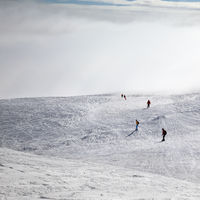 Skiers and snowboarders downhill on snowy slope and sunlight sky in haze