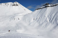 Two skiers and off-piste slope with traces of skis, snowboards and avalanches.