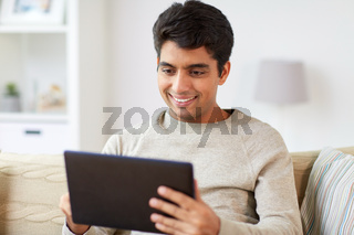smiling man with tablet pc at home
