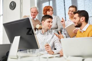 Business Team diskutiert am Computer